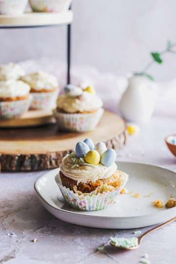 a carrot cupcake being decorated on a plate with chocolate eggs and sprinkles and a tiered serving tray with more cupcakes behind it