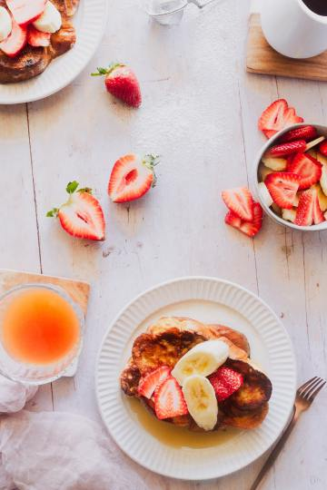 overhead shot of two plates of french toast with a cup of juice and slices of strawberries and fruit