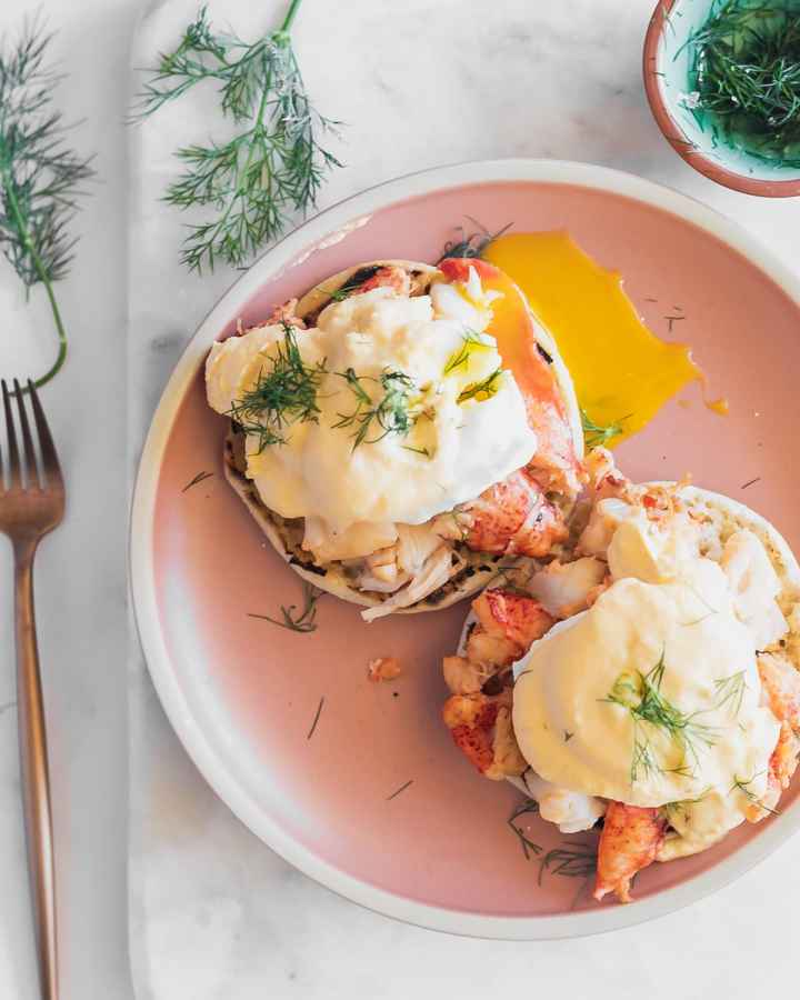 overhead view of eggs benedict with lobster on a plate, garnished with dill