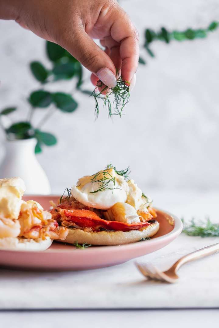 lobster eggs benedict topped with hollandaise sauce being garnished with fresh dill