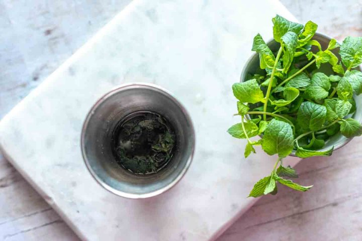 overhead view of muddled mint in a julep cup