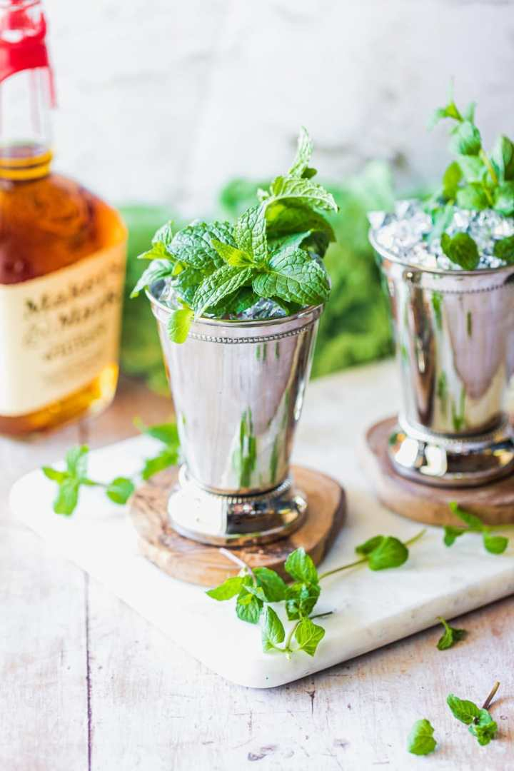 two kentucky derby style mint juleps garnished with mint sprigs