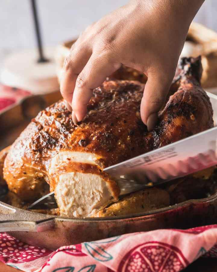 roasted million dollar chicken being carved in pan