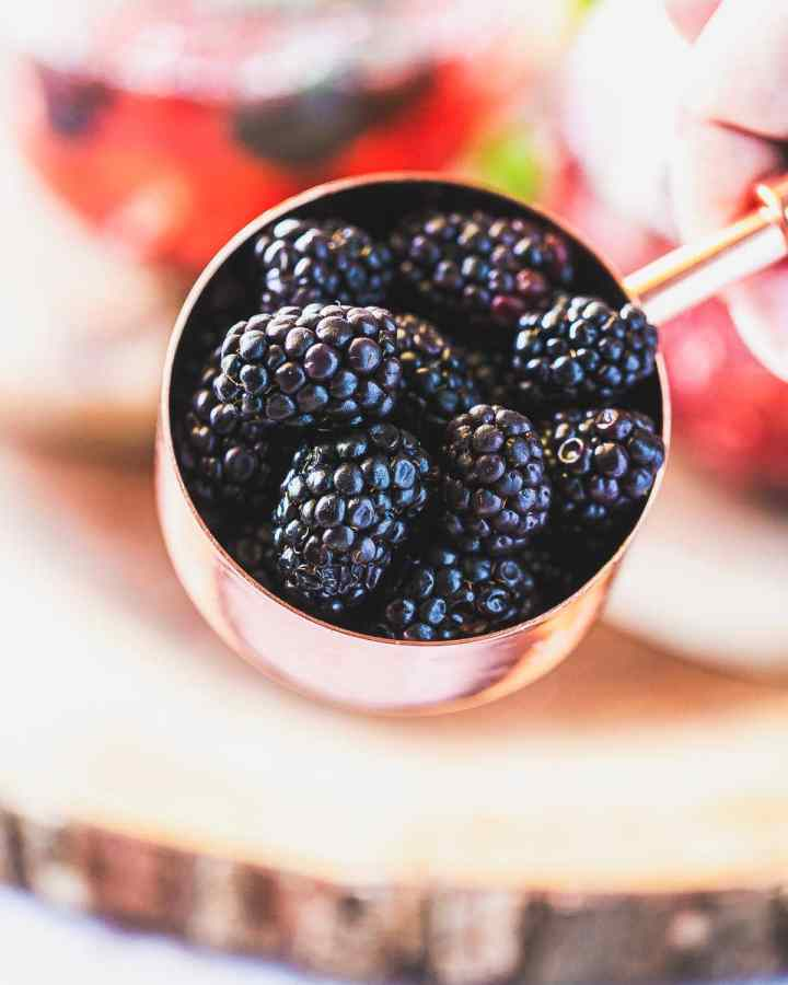 a copper measuring cup filled with fresh blackberries