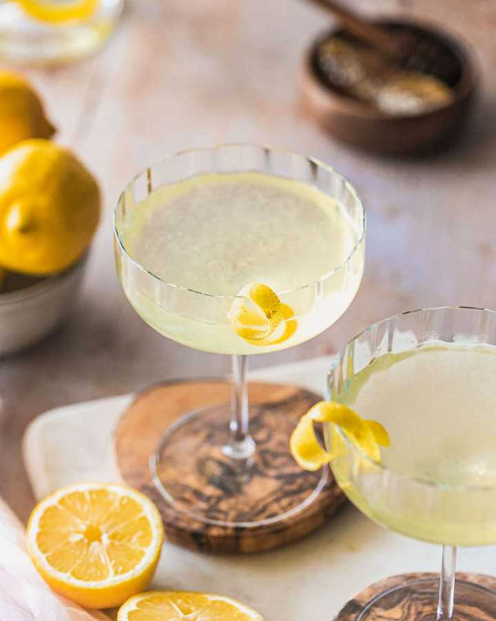 coupe glasses on wood coasters garnished with lemon twists