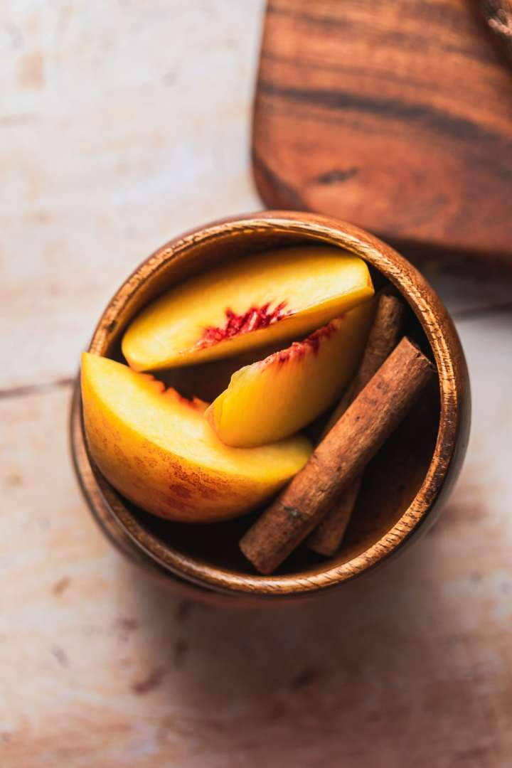 close up show of slices of peaches and cinnamon sticks in a wooden bowl