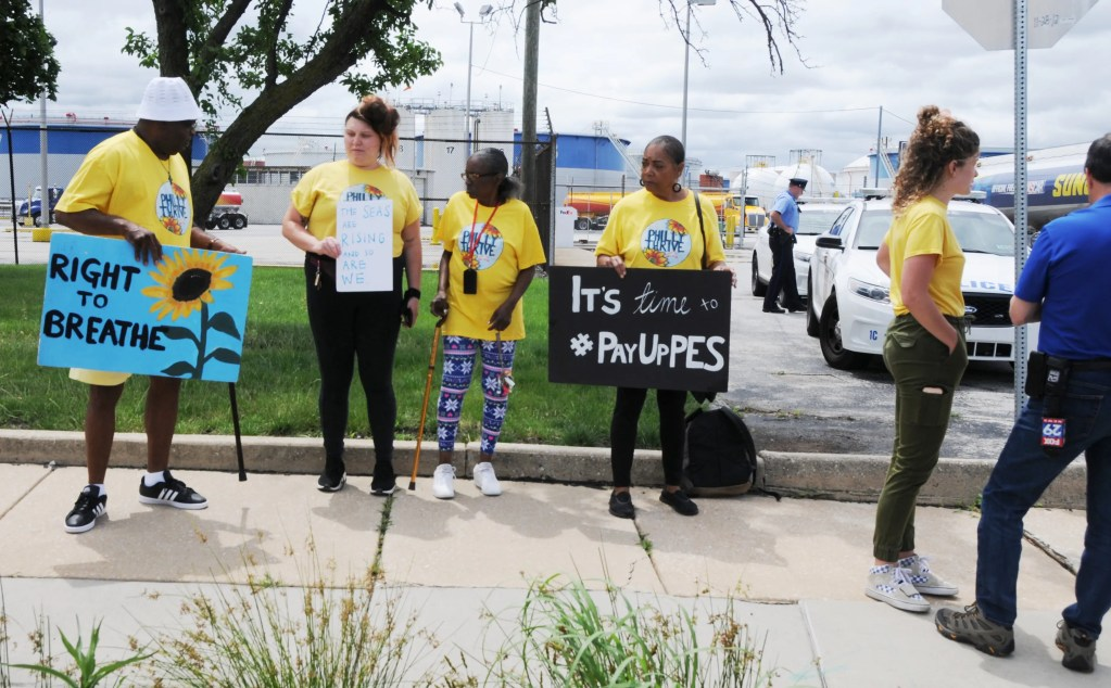 """Photo:  South Philly activist Sylvia Bennett of  Philly Thrive (center) protests outside the entrance to the Phila. Energy  Solutions Plant on Passayunk Avenue after the massive explosions there on the  morning of June 21.  """"It was 'boom,  boom, boom' and I was rocked out of my bed!"""" she said.  Philly Thrive spokesperson Alexa Ross  (right) gets the message across to a TV10 reporter."""