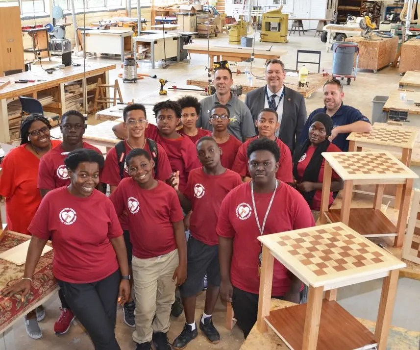 """Young people – mostly from SW schools – display the checkerboard topped utility tables they constructed at the """"Hammers with Hearts"""" carpentry training week at Williamson College of the Trades in Media.  The program was sponsored by The Common Place and Wayne Presbyterian Church.    Back row right are Mike Rounds, President of Williamson, and Mike Neville, Director of Carpentry"""