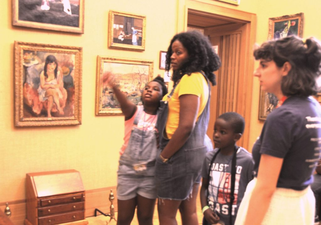 Guide Sara Bloom (left) with the Hall family on their special tour of the Barnes Foundation art museum arranged through the Free Library.   They were particularly attracted to paintings by Horace Pippin (high on the wall behind them) who turned out to be an African American painter who had studied under Dr. Albert Barnes, founder of the museum.
