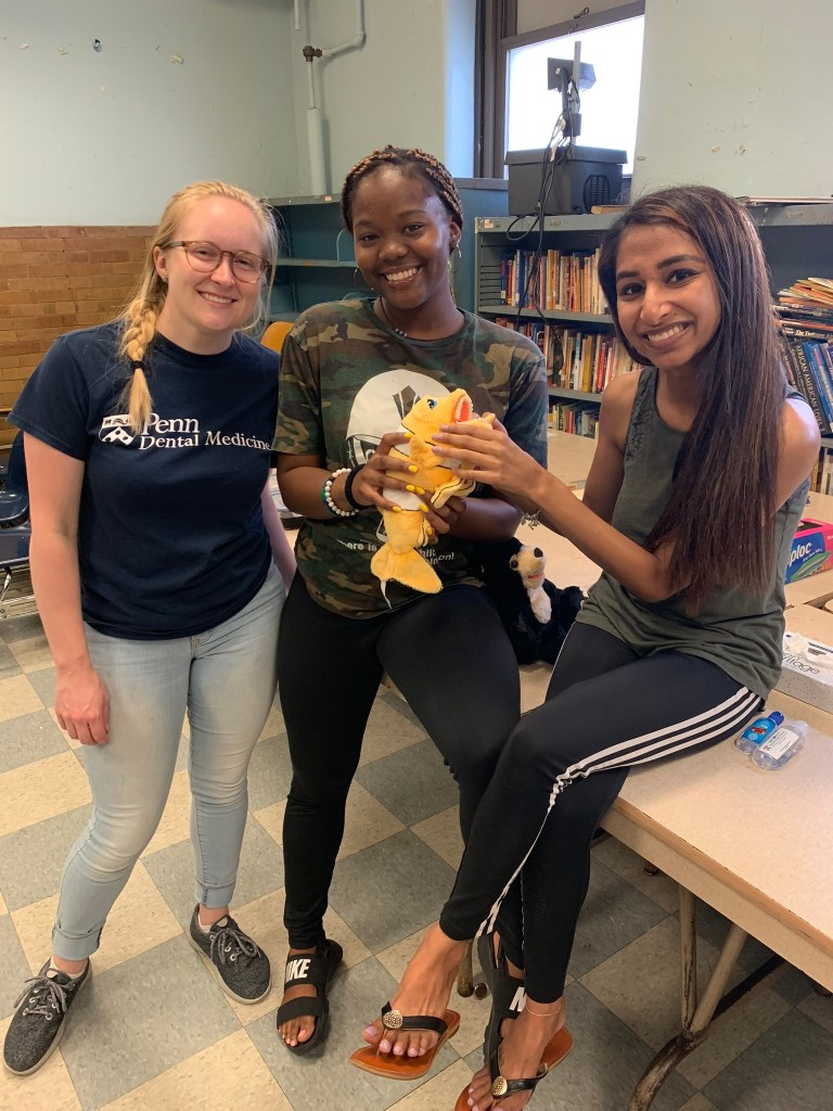 BTG Interns- Kate, Jaylen, and Anjali- pose with Oscar the Fish. He is used to demonstrate proper tooth brushing and flossing technique for the students.