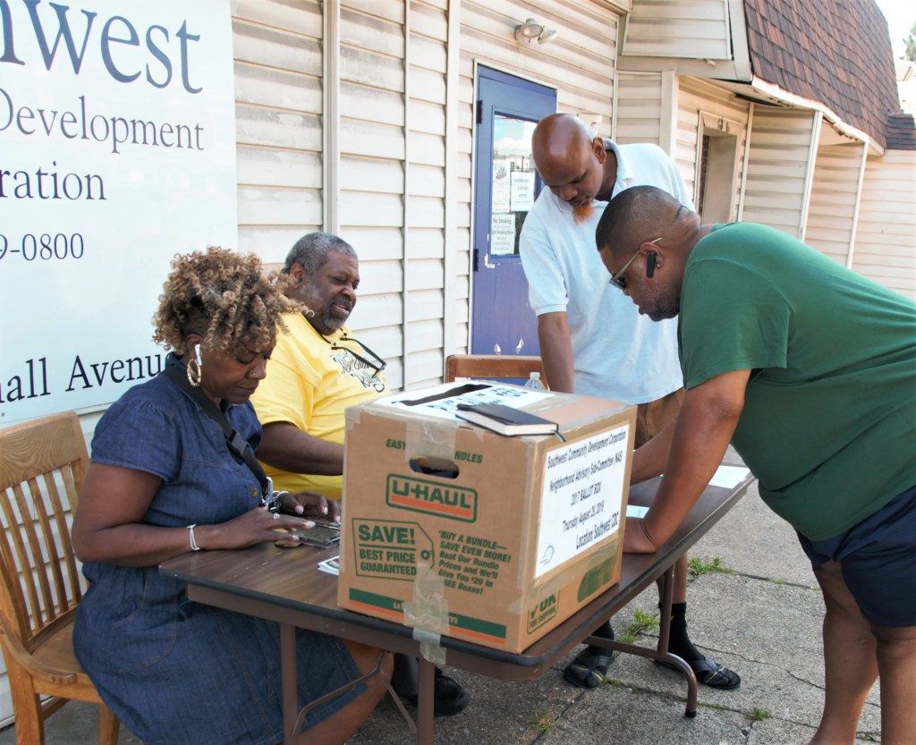 Voters line up outside Southwest CDC on Paschall Avenue to select new members of the local Neighborhood Advisory Sub-Committee (NAS). Pictured are candidate Adriane Park, NAS Coordinator Mark Harrell, and residents Akeem and Marvin (signing his ballot.)