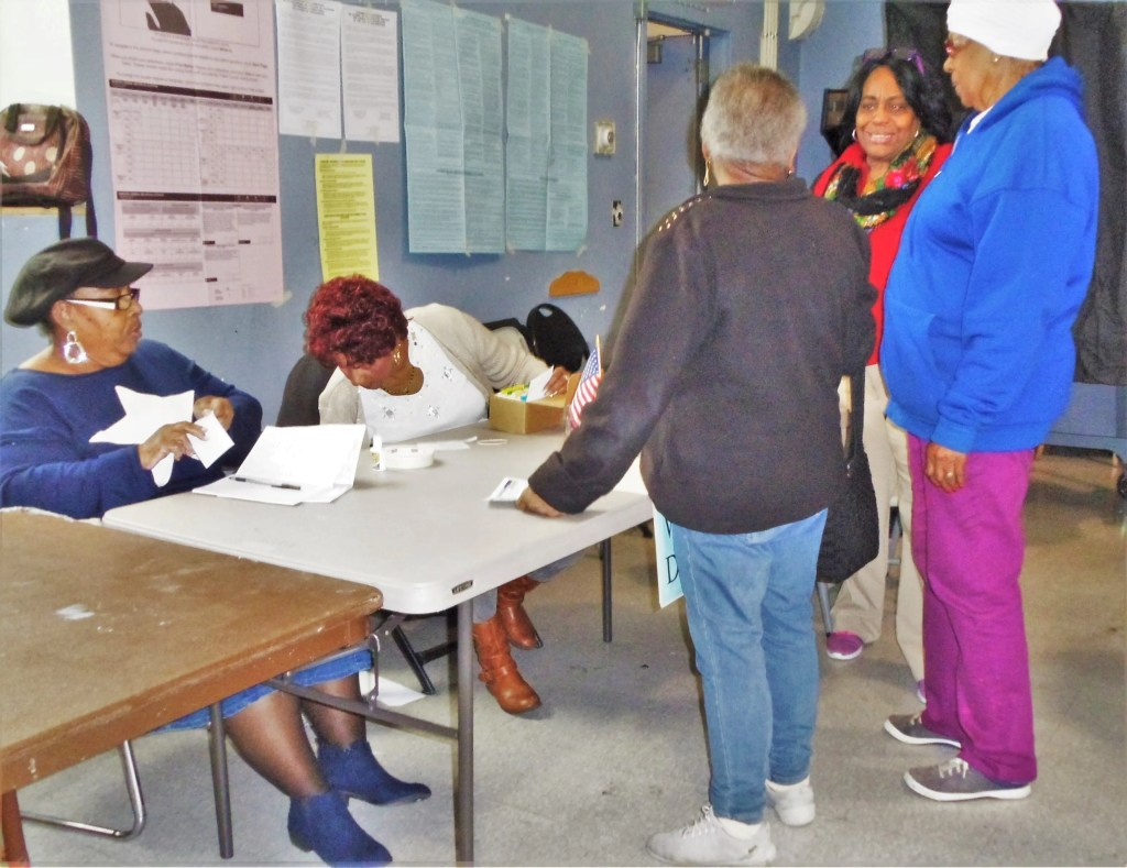 Poll workers explain the new paper ballot system to waiting voters at a Southwest polling place. While there are problems to be worked out before the primary and general elections of 2020, the general verdict was the back-up paper ballots represented a positive change.