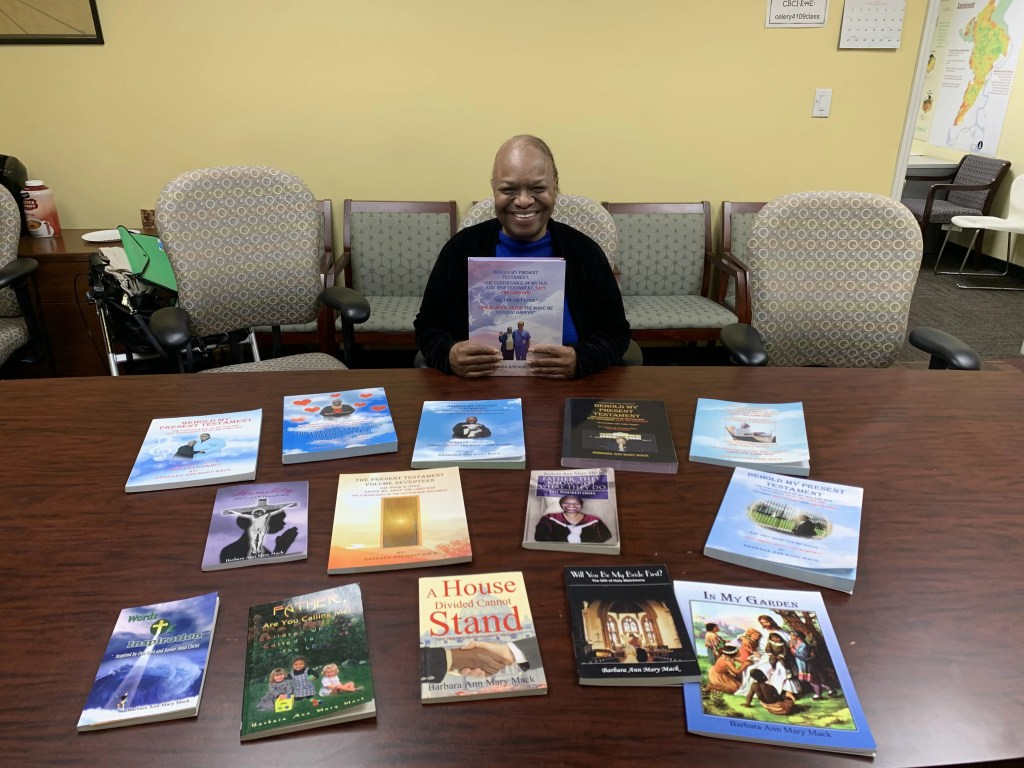 Barbara Ann Mary Mack sitting in front of a small assortment of her published books