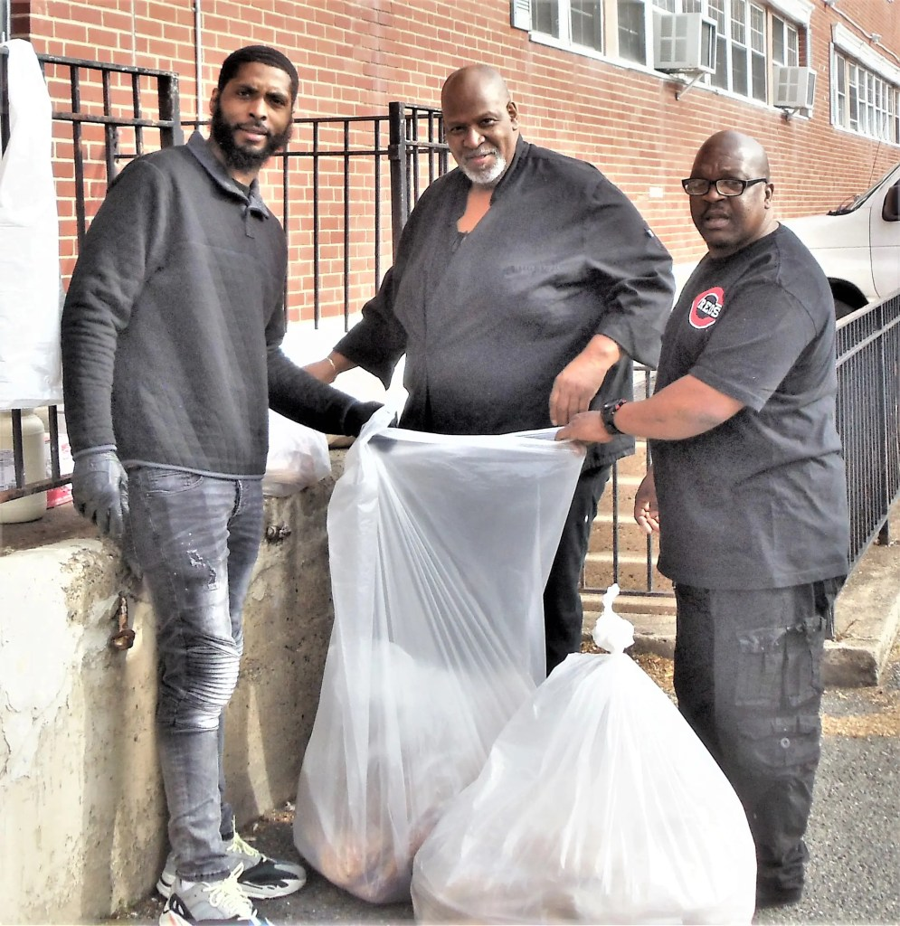 Chef Ricky Hill (Center) and his team at the Outley House Men's Shelter Team bag up bagels collected from suburban bakeries