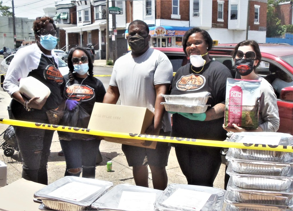 Hiding graciously behind their Philadelphia Auto and Parole face masks are that organization's emergency food distribution team at 5224 Woodland Ave., Jermaine Womack, Chenice Rogers-Womack, Christina Womack, Evelyn Mouzone, and Emily Callaghan.