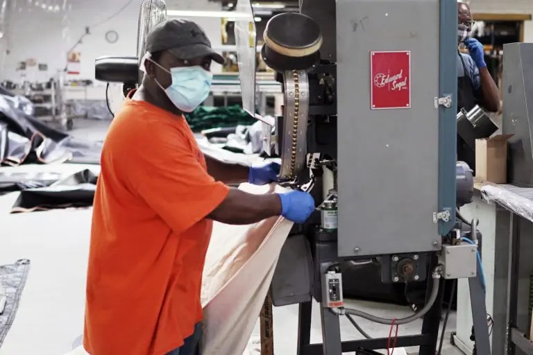 Employee operating the grommet machine at D.C. Humphrys