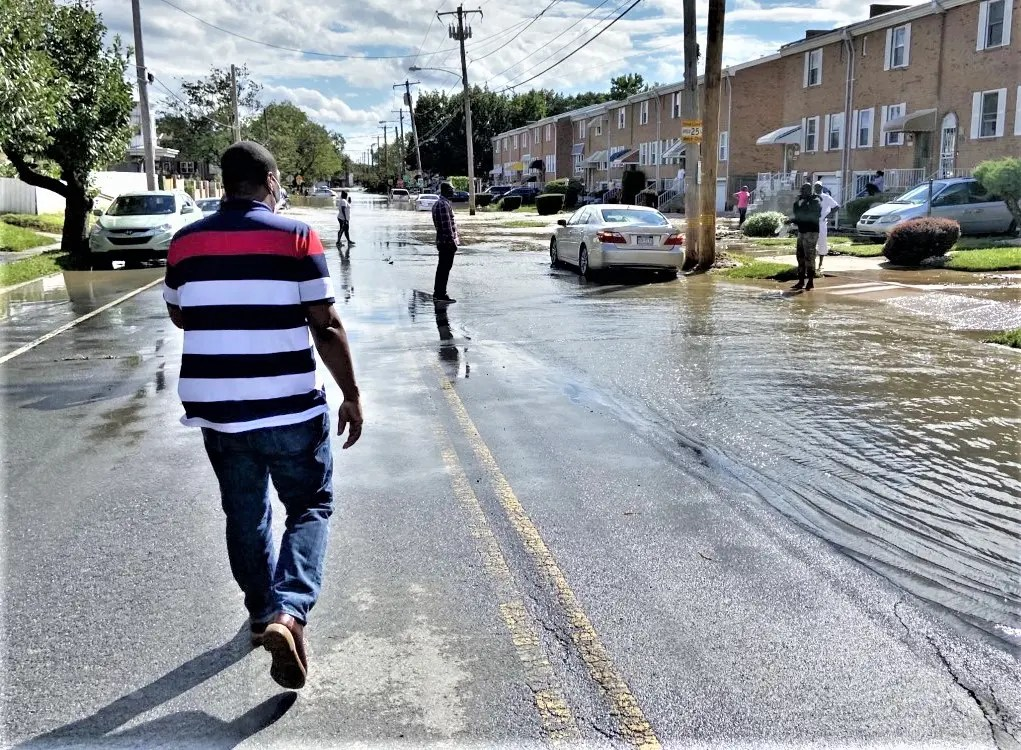 Councilman Kenyatta Johnson strides down an Eastwick street to discuss with residents the impact of Hurricane Isaias on their flooded homes. Flood risks in Eastwick have been a major community concern for decades.