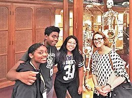 Summer Undergraduates Minority Research high school students with skeletons of a giant and a dwarf are Rayanna Russell, Bonner-Prendergast; Robert Melton, Bartram; and Daisy Hernandez, Audenried; with SUMR Program Director Joanne Levy.