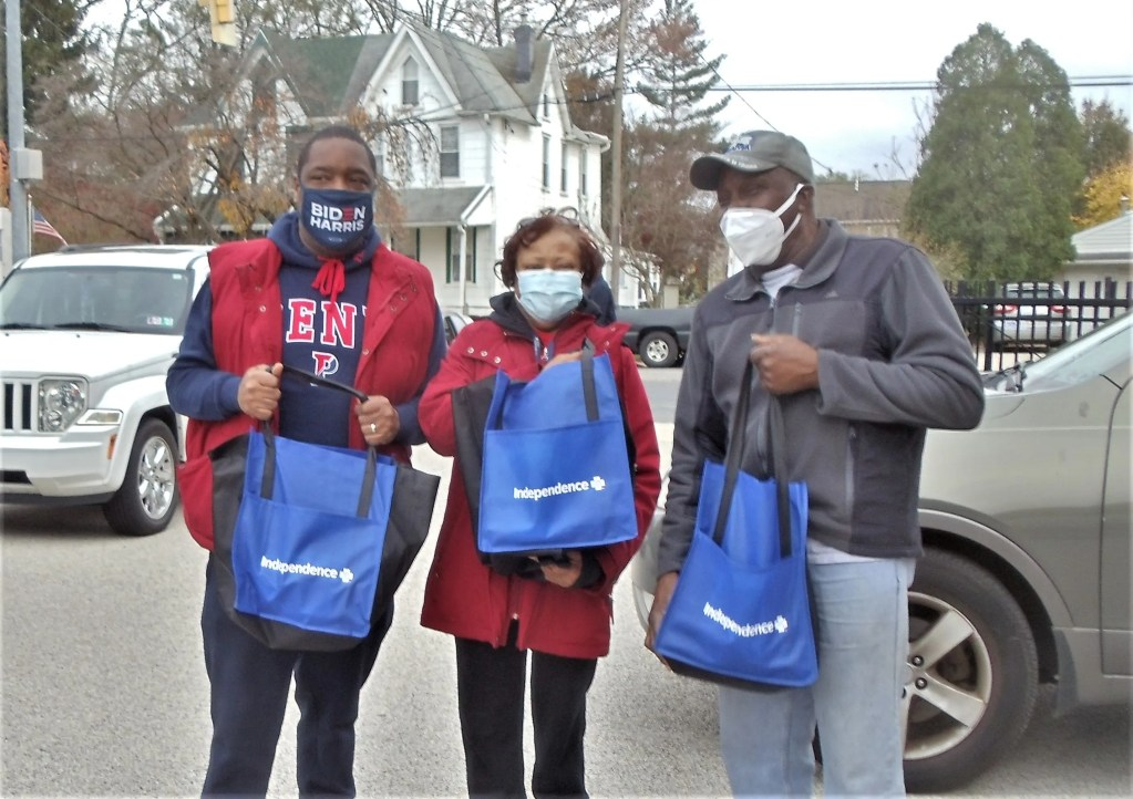 Councilman Kenyetta Johnson (left) with volunteer Carolyn Mosely and community leader Earl Wilson prepare to safely place frozen turkeys in the cars of Southwest residents at the Penrose School in Eastwick.