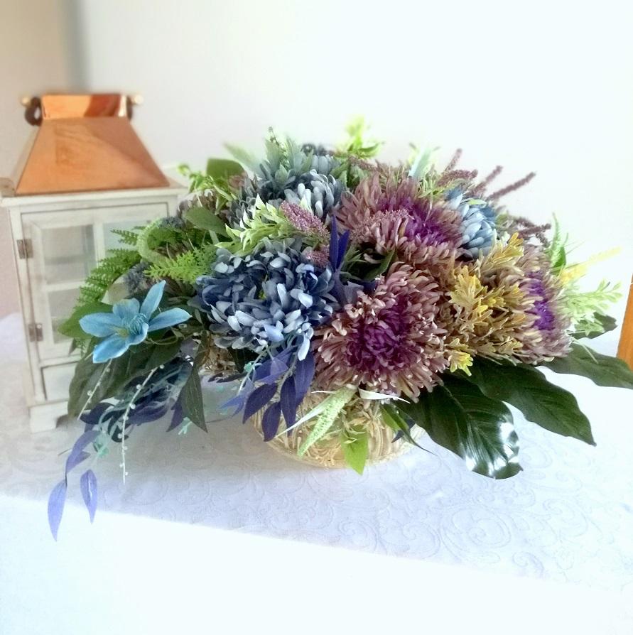 Kompozycja kwiatowa jesienne chryzantemy nr. 183 Kompozycja kwiatowa jesienne chryzantemy nr. 183 jest to kompozycja kwiatowa utrzymana w przpięknychj zgaszonych kolorach fioletu, szarości niebieskiego. Najnowsza kolekcja chryzantem przeznaczona zarówno do jesiennych dekoracji naszych wnętrz jak i na cmentarz. Kompozycja kwiatowa umieszczona została w ozdobnej, betonowej donicy z motywwem monstery. Kwiaty pierzaste w pięknych kolorach uzupełnione zostały paprocią i eukapiptusem.Jest to nowoczesna dekoracja kwiatowa o zgaszonych nostalgicznych kolorach. Zastosowanie elementów zielonych w kilku odcieniach podkreśla kolorystykę kompozycji. Bukiet jest bardzo duży. Wszystkie kwiaty wykorzystane w kompozycji to wysokiej jakości sztuczne kwiaty. Wymiary kompozycji DŚrednica ok 70 cm wysokość:47 cm