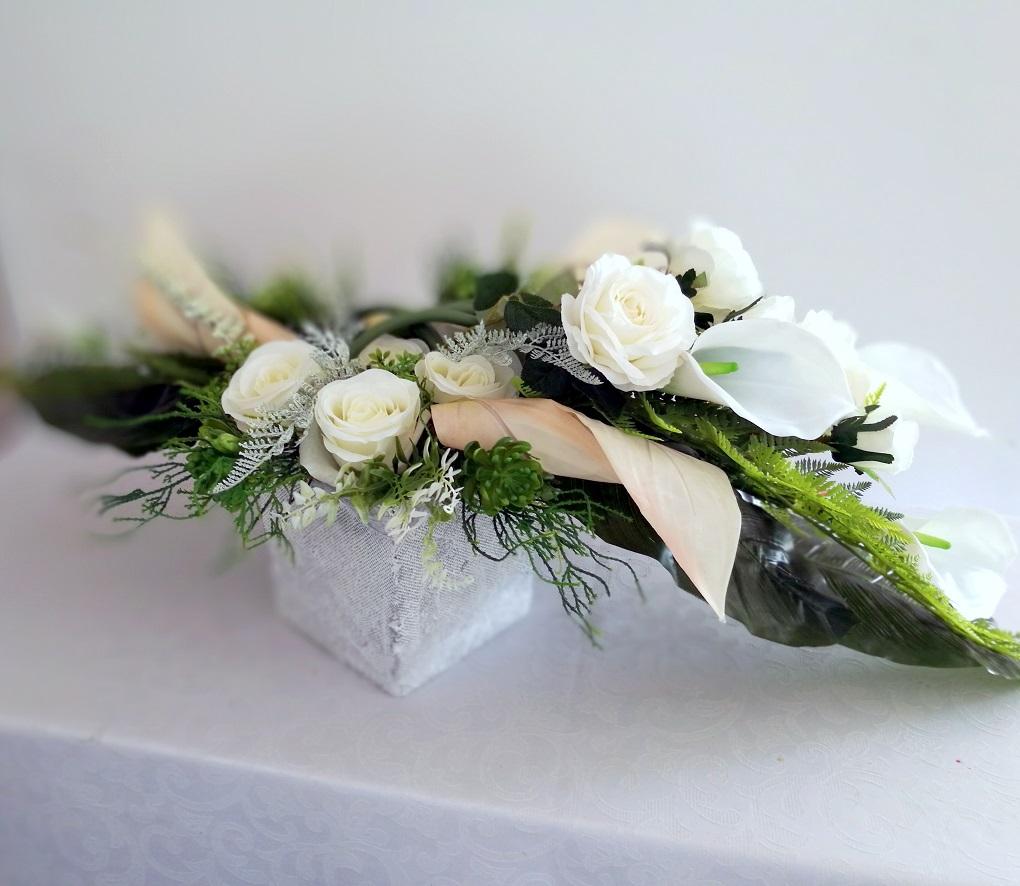 Elegancki Stroik nagrobny Biel nr 350 Elegancki Stroik nagrobny Biel nr 350 jest to unikatowa i nietuzinkowa kompozycja kwiatowa. Stroik leżący to niezwykle elegancka i duża dekoracja. Na dekorację nagrobną składają się głównie róże , kalie uzupełnione elementami zielonymi. Elementy zielone zastosowane w tej kompozycji nagrobnej to: paproć,gumowe sukulenty oraz liście monstery, uzupełnione drobnymi kwiatami i owocami. Całość osadzona jest w betonowej donicy by zachować stabilność przy zmiennych, typowych dla naszego klimatu, warunkach pogodowych . Prosta forma nadaje kompozycji lekkości i elegancji. Kalie i róże pięknie ze sobą współgrają tworząc harmonijną całość. Stroik praktycznie na każdym nagrobku będzie się prezentować pięknie ze względu na swoją okazałą formę oraz piękną kolorystykę. Wszystkie kwiaty wykorzystane w kompozycji to wysokiej jakości sztuczne kwiaty. Jest to elegancka alternatywa dla tradycyjnych wiązanek, sprzedawanych pod cmentarzami. Jeżeli spodobała się Wam nasza kompozycja Elegancki Stroik nagrobny Biel nr 350 możemy dla Was przygotować w komplecie inne elementy dekoracyjne, takie jak wianki, stroiki, bukiety itp., zgodnie z Waszymi życzeniami, które możecie nam przekazać. Wymiary kompozycji Długość kompozycji leżącej ok 100 cm Wysokość ok. 36 cm Jest to elegancka alternatywa dla tradycyjnych wiązanek, sprzedawanych pod cmentarzami. Podsumowując, jeżeli odpowiada Państwu ta kolorystyka, ale chcielibyście zobaczyć również podobne alternatywy – mogą je znaleźć Państwo tutaj: Zestaw na cmentarz w bieli Stroik i bukiet Spokojny sen nr. 151 Kompozycja nagrobna w bieli nr. 135 Podobna wersja kolorystyczna tego zestawu, ale z nutą innych odcieni dostępna jest tutaj: Kompozycja nagrobna nr. 116 Kompozycja kwiatowa białe i amarantowe kalie nr. 122 Kompozycja na cmentarz z bukietem nr. 124 Z kolei mniejszą wersję tej dekoracji na grób, ale w rozmiarze M mogą Państwo obejrzeć pod tym linkiem: Zestaw w bieli rozmiar M nr. 114 Ze względu na to, że nasze k