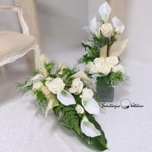 Elegancki Stroik nagrobny Biel z bukietem nr 376 Elegancki Stroik nagrobny Biel nr 350 jest to unikatowa i nietuzinkowa kompozycja kwiatowa. Stroik leżący to niezwykle elegancka i duża dekoracja. Na dekorację nagrobną składają się głównie róże , kalie uzupełnione elementami zielonymi. Elementy zielone zastosowane w tej kompozycji nagrobnej to: paproć, gumowe sukulenty oraz liście monstery, uzupełnione drobnymi kwiatami i owocami. Całość osadzona jest w betonowej donicy by zachować stabilność przy zmiennych, typowych dla naszego klimatu, warunkach pogodowych . Prosta forma nadaje kompozycji lekkości i elegancji. Kalie i róże pięknie ze sobą współgrają tworząc harmonijną całość. Stroik praktycznie na każdym nagrobku będzie się prezentować pięknie ze względu na swoją okazałą formę oraz piękną kolorystykę. Bukiet osadzony w plastikowym we wkładzie do wazonu, Wszystkie kwiaty wykorzystane w kompozycji to wysokiej jakości sztuczne kwiaty. Jest to elegancka alternatywa dla tradycyjnych wiązanek, sprzedawanych pod cmentarzami. Jeżeli spodobała się Wam nasza kompozycja Elegancki Stroik nagrobny Biel nr 350 możemy dla Was przygotować w komplecie inne elementy dekoracyjne, takie jak wianki, stroiki, bukiety itp., zgodnie z Waszymi życzeniami, które możecie nam przekazać. Wymiary kompozycji Długość kompozycji leżącej ok 100 cm Wysokość ok. 36 cm bukiet wysokość 67 cm Nie ma dwóch takich samych Każda z naszych dekoracji jest wykonywana ręcznie, więc gwarantujemy, że dekoracja dostarczona Wam będzie jedyna w swoim rodzaju. Ze względu na to, że nasze kompozycje wykonywane są za każdym razem ręcznie przez florystę oraz sezonowość wykorzystywanych w kompozycjach dodatków – kompozycja przygotowana dla Państwa może delikatnie różnić się od przedstawionej na zdjęciu. Gwarantujemy natomiast jakość i estetykę wykonania Państwa zamówienia. Wszystkie kwiaty wykorzystane w kompozycji to wysokiej jakości sztuczne kwiaty. Jest to elegancka alternatywa dla tradycyjnych wiązanek, sprzedawanych 