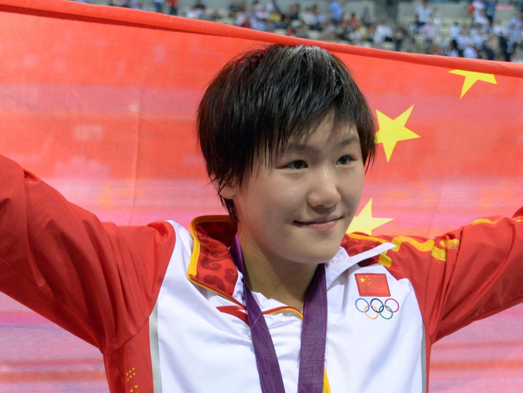 Jul 31, 2012; London, United Kingdom; Ye Shiwen (CHN) poses with her gold medal and a China flag after winning the women's 200m individual medley finals during the London 2012 Olympic Games at Aquatics Centre. Mandatory Credit: Kirby Lee-USA TODAY Sports