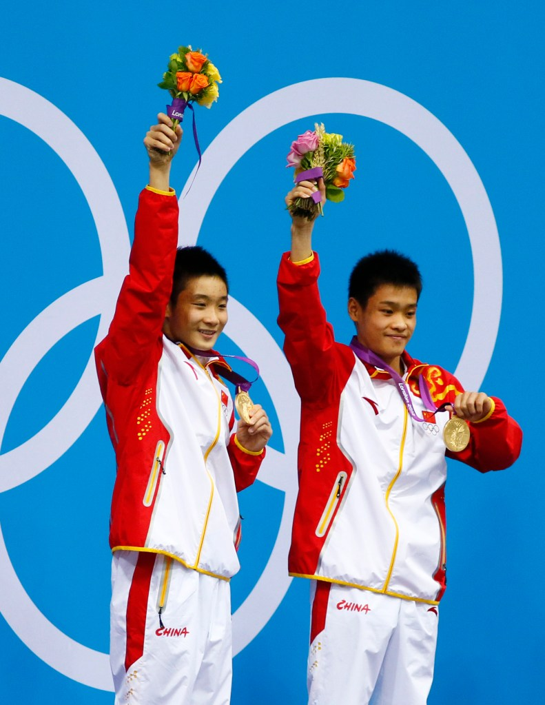 Jul 30, 2012; London, United Kingdom; Cao Yuan and Zhang Yanquan (CHN) celebrate with their gold medals after winning the men's 10m platform synchronized diving final during the London 2012 Olympic Games at Aquatics Centre. Mandatory Credit: Rob Schumacher-USA TODAY Sports