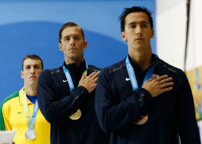 Jul 17, 2015; Toronto, Ontario, CAN; Nicholas Thoman of the United States (middle) and Eugene Godsoe of the United States (right) stand for the national anthem after the men's 100m backstroke final the 2015 Pan Am Games at Pan Am Aquatics UTS Centre and Field House. Mandatory Credit: Rob Schumacher-USA TODAY Sports