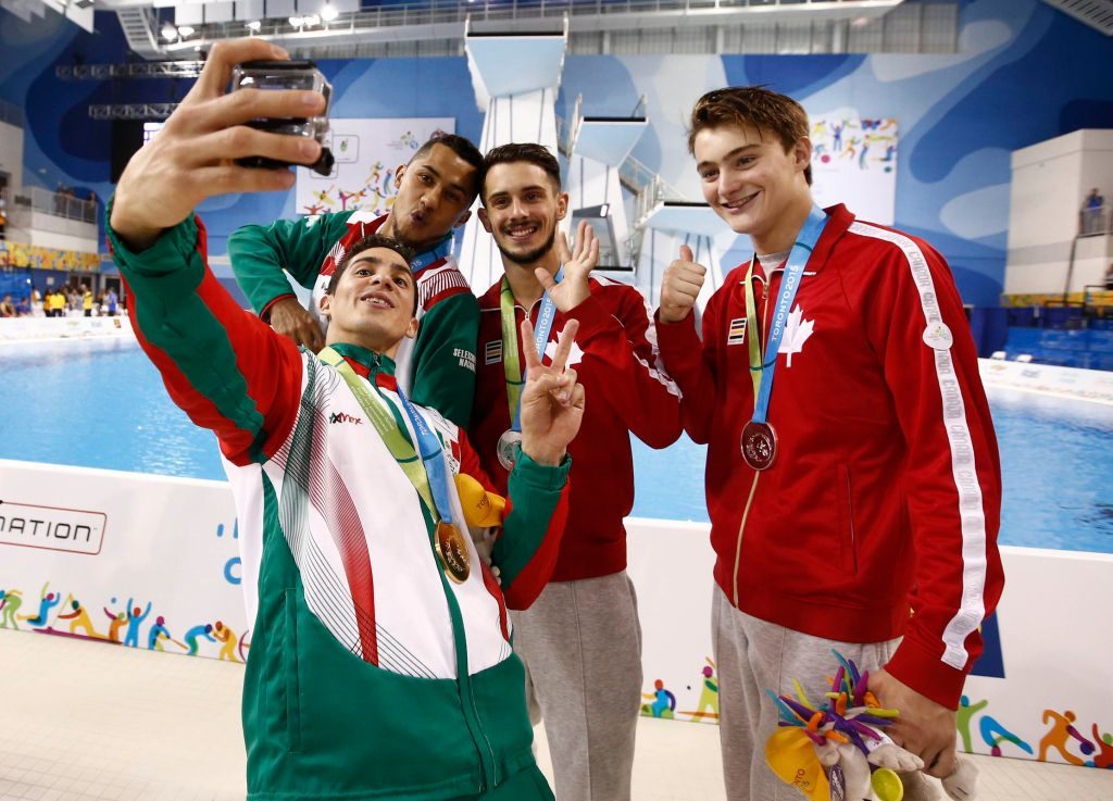 Jul 13, 2015; Toronto, Ontario, USA; Jahir Ocampo and Rommel Pacheco of Mexico (left) pose for a photo with Philippe Gagne and Francois Imbeau-Dulac of Canada after the men's synchronised diving 3m springboard final the 2015 Pan Am Games at Pan Am Aquatics UTS Centre and Field House. Mandatory Credit: Rob Schumacher-USA TODAY Sports