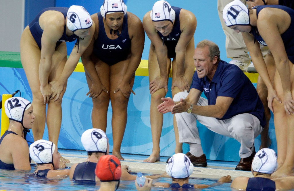 USA's head coach Guy Baker talks with his players during a time out in a preliminary round women's water polo match against Italy at the Beijing 2008 Olympics in Beijing, Wednesday, Aug. 13, 2008. The teams tied 9-9. (AP Photo/Mark Humphrey)