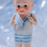Nippon all-bisque, boy bather doll in a blue sun suit