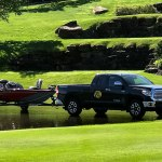 Tracker boat on trailer pulled by truck in pond