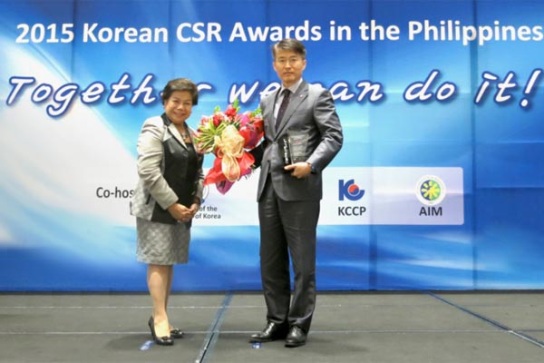 LGEPH's Managing Director Sung Woo Nam with Philippine Economic Zone Authority (PEZA) director general Lilia B. De Lima accepting the Rescue and Aid Award during the 2015 Korean CSR Awards in the Philippines.