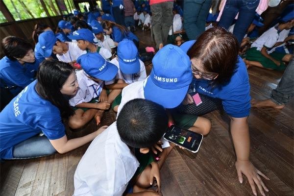 Samsung volunteers helping children with the alphabet game on Samsung tablets