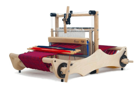 A wooden weaving loom with red and blue cloth on it.
