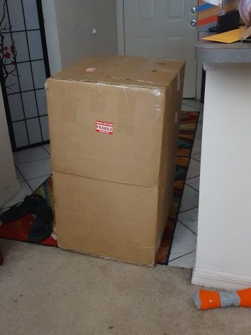 A tall cardboard box sitting in the apartment entryway. It has FRAGILE stickers on it. To the left is a red bookshelf. To the right is the breakbast bar.