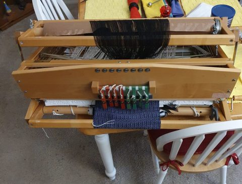 A folded-up weaving loom sitting on a dining table. There's a purple and black scarf project on it.