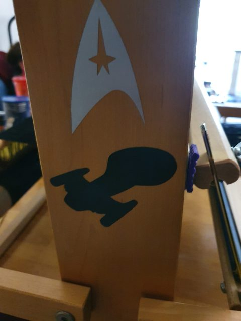 The side of a loom's castle.  Decals are on it, of the Star Trek Starfleet Command logo and the Voyager spaceship.