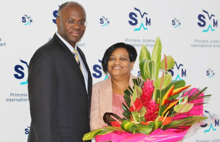 Governor Eugene Holiday poses with his successor at SXM Airport, managing director Regina LaBega after presenting her with a bouquet of flowers on occasion of the airport's 70th anniversary celebrations. (SXM Airport photo)