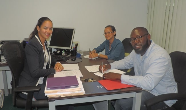 (L-R) Sandy Offringa, SXM Legal Officer, Suzy Kartokromo, Acting Manager of Marketing & Customer Service, and Cleon Frederick, Managing Director of St. Maarten Wrapping Service, at the signing. (SXM photo)