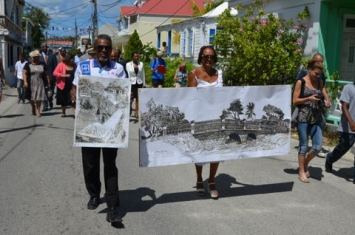 Attorney Patricia Chance-Duzant champions the restoration of the traditional period design for Grand Case Bridge at a support meeting in her native village. Behind her is an enlarged image of the engraving by Roland Richardson that captures the traditional design of the Grand Case Bridge.  (Photo courtesy P. Chance-Duzant)