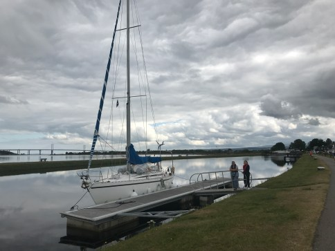 Carpe Diem at the pontoon at the final lock. In the background is Inverness Firth