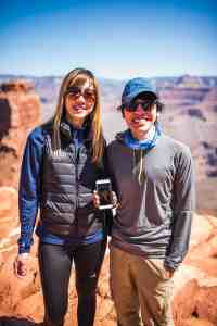Maria and Anson holding a photo of Kent posing in front of the Grand Canyon