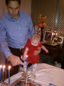 Lighting the Hanukkah candles with her grandpa