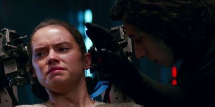 Image description: Kylo Ren tortures Rey, reaching toward her head as he uses the Force to read her mind. Rey looks pained.