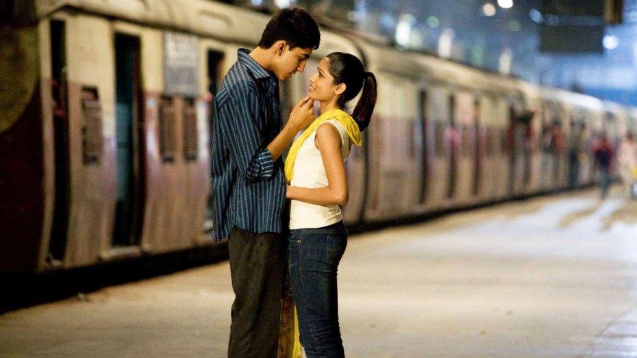 Vignette du film Slumdog Millionaire : un couple entrelacé, dans une gare de train. Le train semble arriver ou partir, et le couple s'apprête à s'embrasser.