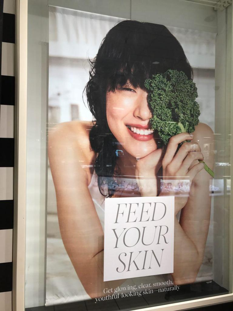 farmacy skincare review skincare superfoods - BEAUTY: Skincare Superfoods Makeover + Farmacy Beauty Skincare Review featured by popular San Francisco beauty blogger, Sylvie in the Skye | Farmacy Beauty Skincare Review + Skincare Superfoods Makeover by top US beauty blog, Sylvie in the Sky: image of Sephora advertisement poster with smiling Asian woman holding a piece of kale.