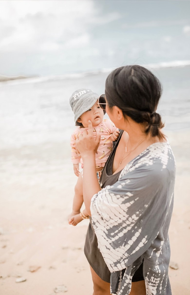 BABY SUN SAFETY featured by top US mommy blogger Sylvie In The Sky | Babyganics by popular San Francisco motherhood blog, Sylvie in the Sky: image of a mom holding her baby next to the ocean.