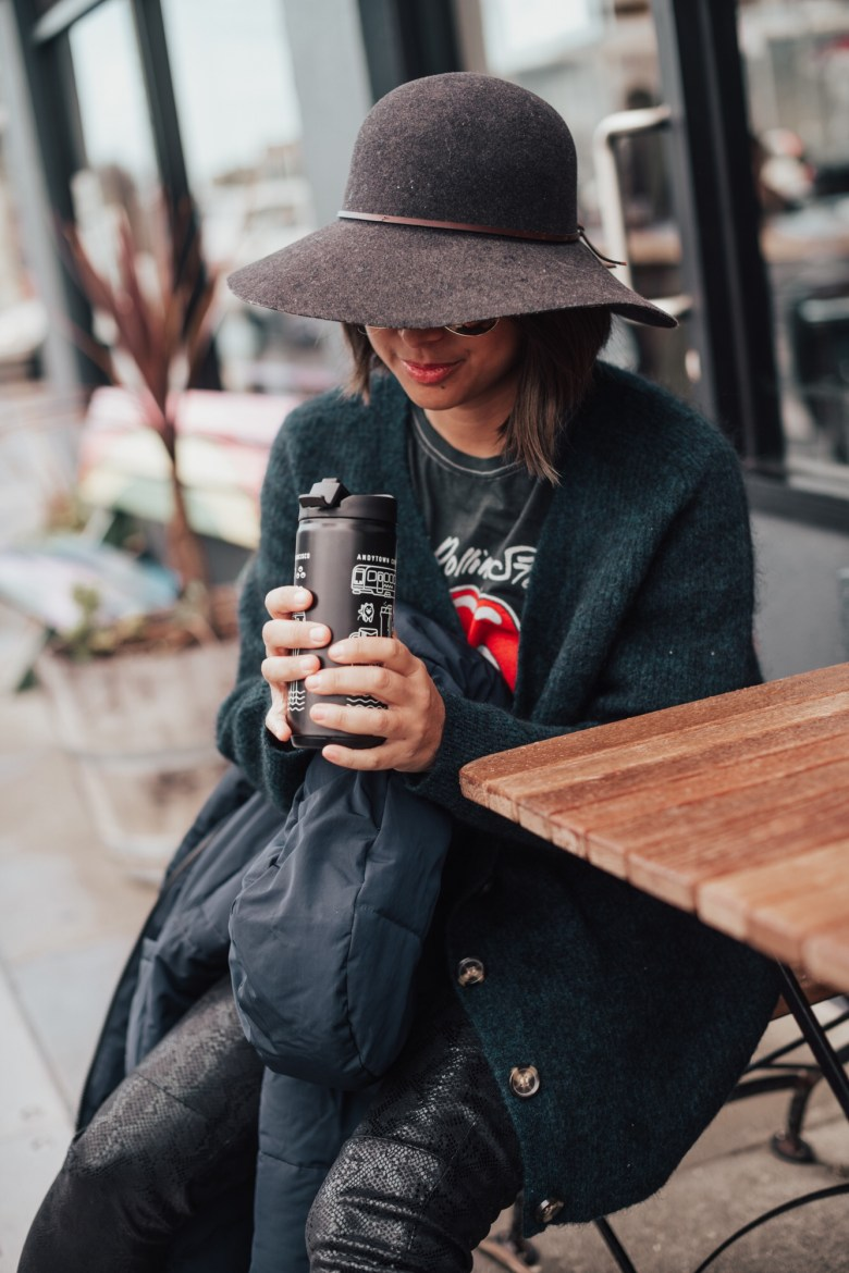 Coffee Gifts by popular San Francisco life and style blog, Sylvie in the Sky: image of a woman wearing a felt hat, baggy black sweater and black pants while sitting outside and holding a black insulated coffee cup.